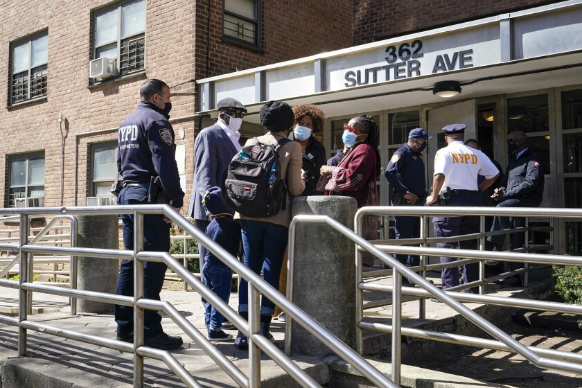 Police officers and community leaders stand outside the building where a man shot the mother of his child and two of her daughters dead before turning the gun on himself, Tuesday, April 6, 2021, in the Brownsville neighborhood of the Brooklyn borough of New York. (AP Photo/Mary Altaffer)