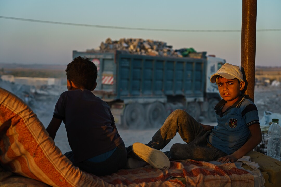 Children who work as laborers sit and rest as a truck brings in debris.