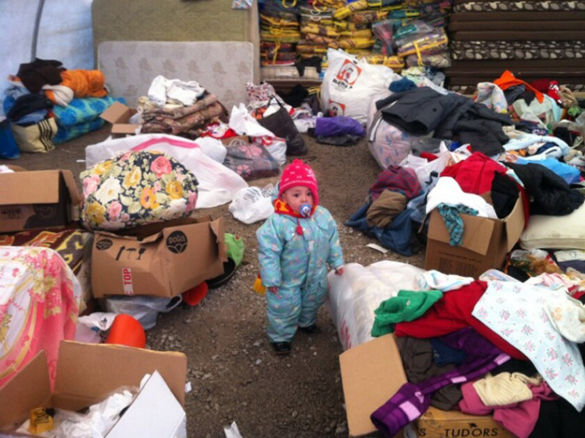 A child stands amid donated items for Uighur migrants in a tent in Kayseri, Turkey. More than 600 Uighurs from China are living in government-supplied apartments in the city, and residents have donated food, furniture and clothing for them.
