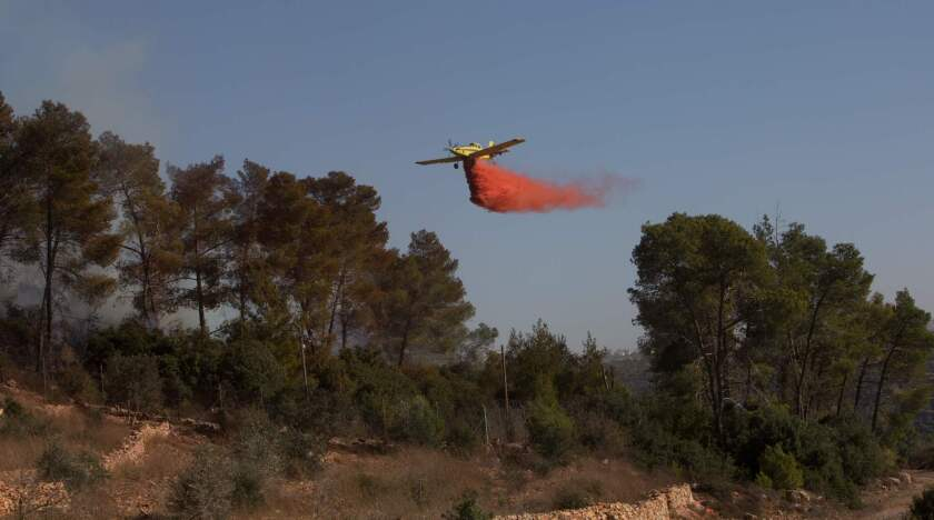 An Israeli firefighting plane helps extinguish a fire over the Halamish settlement, northwest of Ramallah near the village of Nabi Saleh in the occupied West Bank.