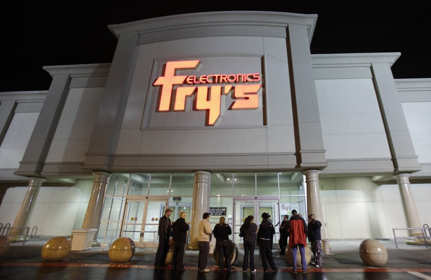 A small crowd begins to gather outside a Fry's Electronics store.