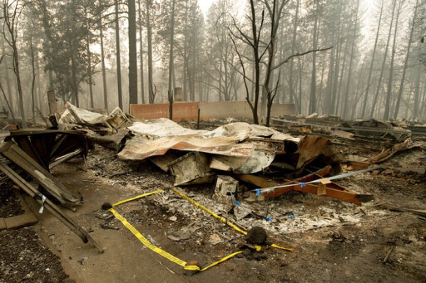 Tape marks a spot where sheriff's deputies recovered the body of a Camp fire victim in Paradise, Calif., last year.
