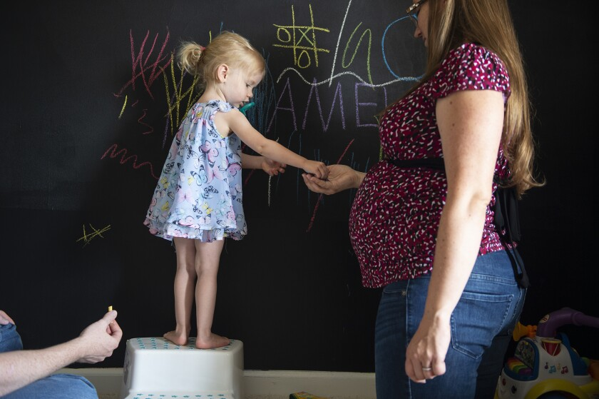 Rebecca Grimm plays chalk with her 2-year-old daughter, Amelia, and husband, Mark, at their home in Westfield, Ind.