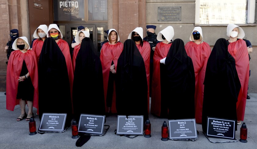 """File-In this file photo from July 24, 2020, women dressed to evoke the feminist dystopian story """"The Handmaid's Tale"""" carry out a symbolic protest after a government minister threatened to pull the country out of an international convention aimed at protecting women from violence, including domestic violence. The treaty is known as the Istanbul Convention and is the work of the Council of Europe, an intergovernmental human rights body. A delegation from the organization has been in Poland this week to assess Poland's adherence to the treaty. (AP Photo/Czarek Sokolowski/file)"""
