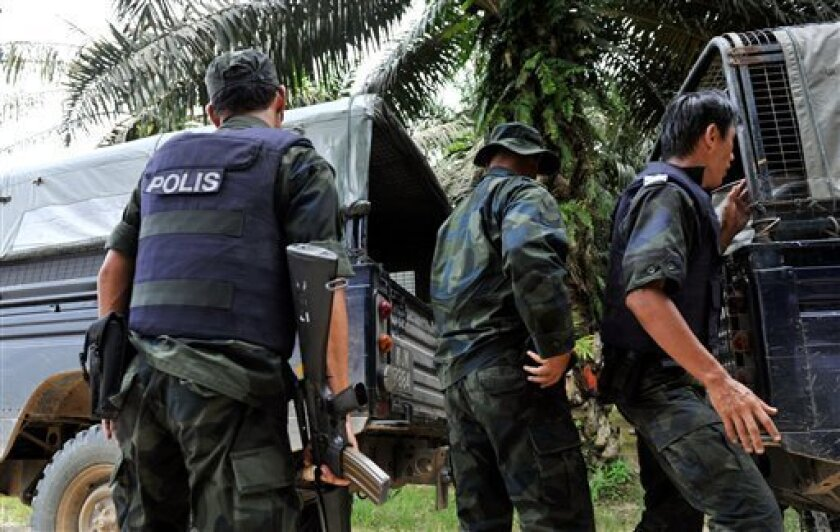 Malaysian police officers move the bodies of two commandoes who were killed in a mortar attack after a exchange of fire between Malaysian security forces and the Sulu sultanate intruders in Tahduo, outside of Lahad Datu, Sabab, Malaysia on, Friday, March 1, 2013. Shooting erupted in Lahad Datu vill