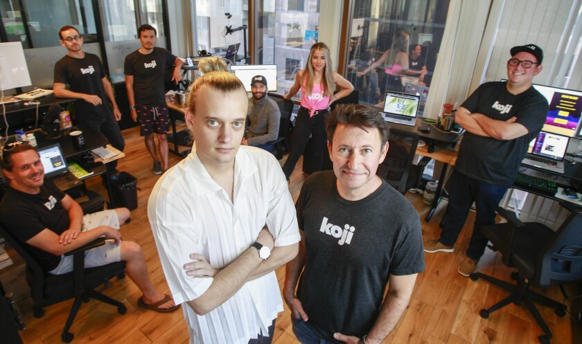 Co-founders Sean Thielen (left) and Dmitry Shapiro stand with staff at Koji, at their WeWork office space in San Diego.