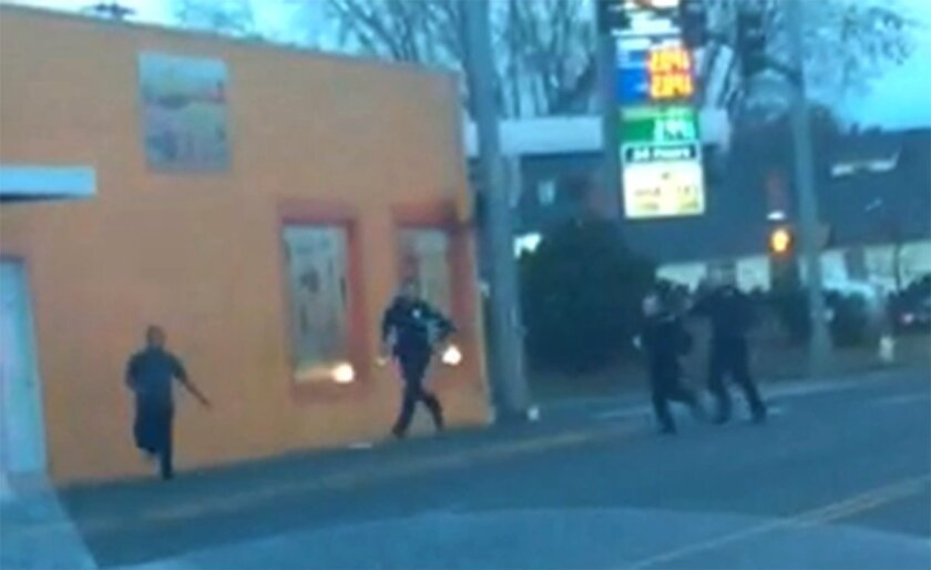 In this still frame taken from a cell phone video provided by Dario Infante and taken on Feb. 10, 2015, Antonio Zambrano-Montes, left, turns to face police officers while running from them in Pasco, Wash. Moments later, Zambrano-Montes was shot and killed. Pasco police said he threw multiple rocks,
