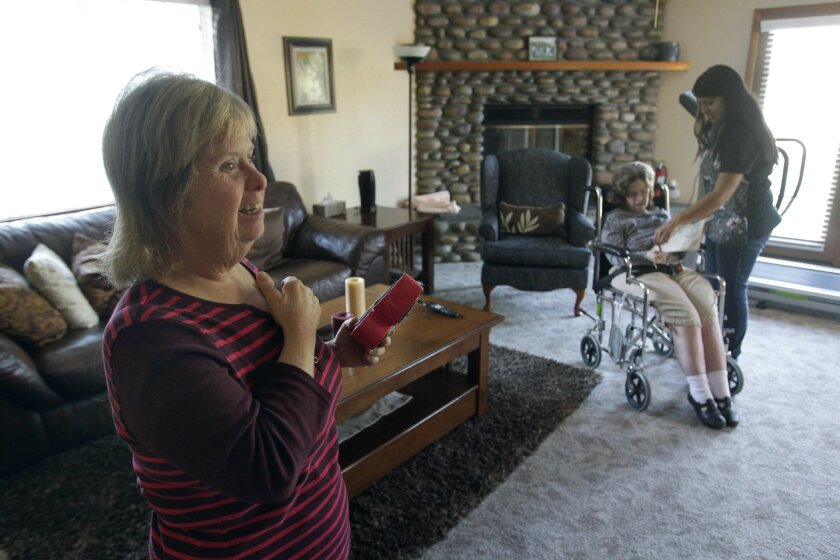 """Kathy Ruef, 54, who has Down syndrome and Alzheimer's disease, waits for the start of her favorite television show """"Friends"""" as Direct Support Professional Diana Perez helps Ruef's housemate Noreen Magner while in the living room at Casa Delight, the all women's home at Noah Homes in Spring Valley"""