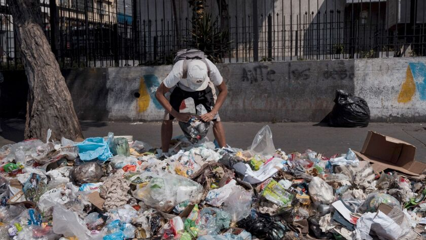 A man scavenges for food in Caracas on February 1, 2019. (Adriana Loureiro Fernandez / For The Times