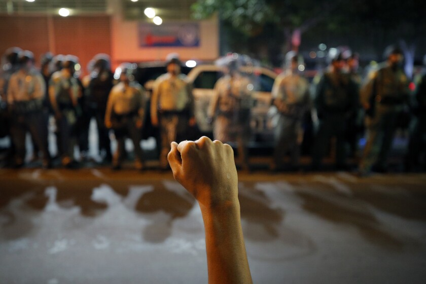 A protester raises his fist during a rally Monday, June 1, 2020, in Las Vegas, against police brutality sparked by the death of George Floyd, a black man who died after being restrained by Minneapolis police officers on May 25. (AP Photo/John Locher)
