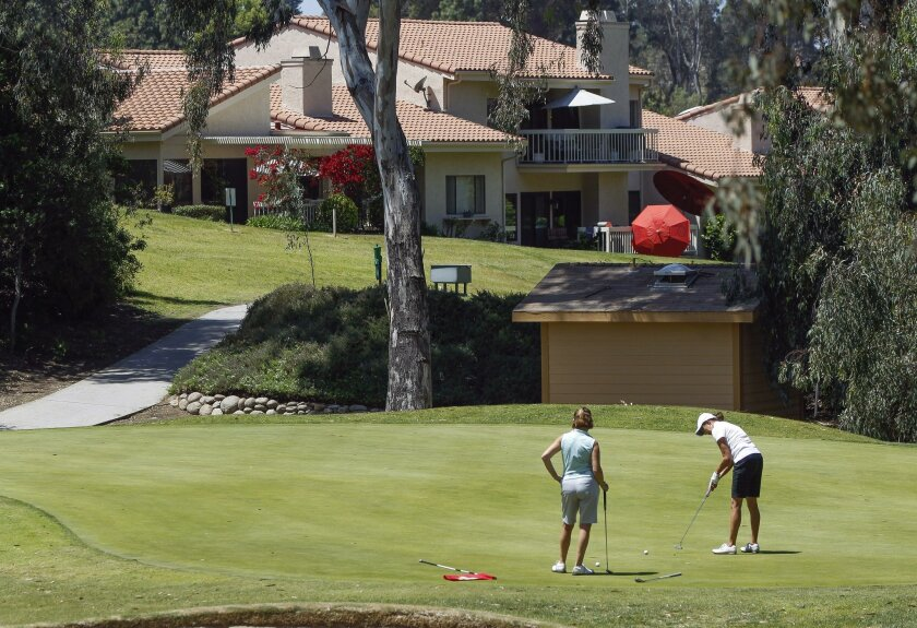 A pair of women putt on a green as they play golf at the StoneRidge Country Club in Poway on Tuesday.