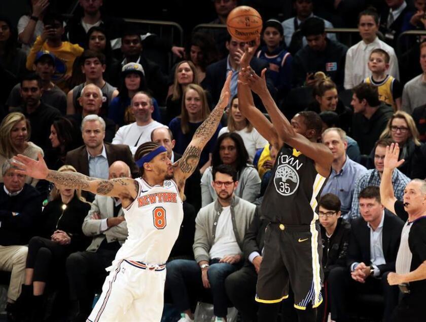 Kevin Durant (d) de Golden State Warriors tira a canasta durante un partido. EFE/Archivo