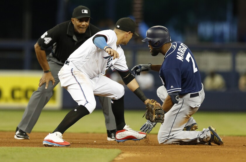 Padres center fielder Manuel Margot slides into second base with a double as Miami Marlins shortstop Miguel Rojas applies a late tag.