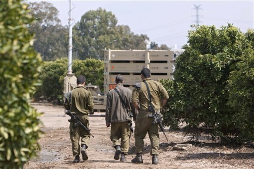 """This photo taken Tuesday, March 27, 2012 shows Israeli soldiers walk past an Iron Dome short-range rocket interceptor battery, deployed in central Israel. The Pentagon says it will ask Congress for more money for Israel's anti-rocket system known as the """"Iron Dome."""" (AP Photo/Oded Balilty)"""