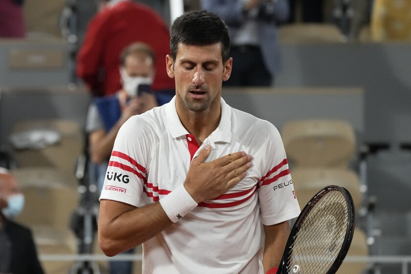 Serbia's Novak Djokovic puts his hand on his heart after defeating Spain's Rafael Nadal in their semifinal match of the French Open tennis tournament at the Roland Garros stadium Friday, June 11, 2021 in Paris. Novak Djokovic won 3-6, 6-3, 7-6 (4), 6-2. (AP Photo/Michel Euler)