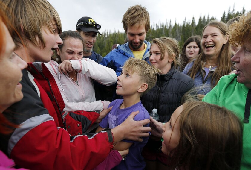 Malachi Bradley, center, smiles at his brother Levi as he is reunited with his family, Monday, Aug. 24, 2015, in Uintah County, Utah, after being lost near the Wyoming border on Sunday. (Ravell Call/The Deseret News via AP) SALT LAKE TRIBUNE OUT; MAGS OUT; MANDATORY CREDIT