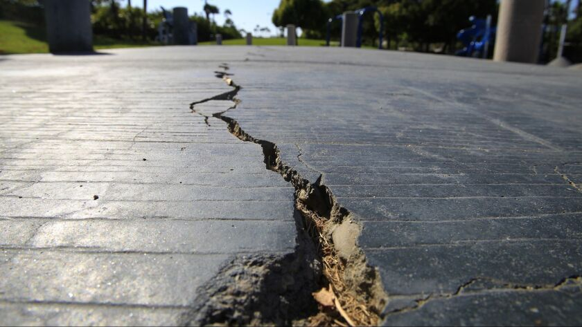 A long crack splits the sidewalk at the Discovery Well Park in the SeaCliff area of Huntington Beach