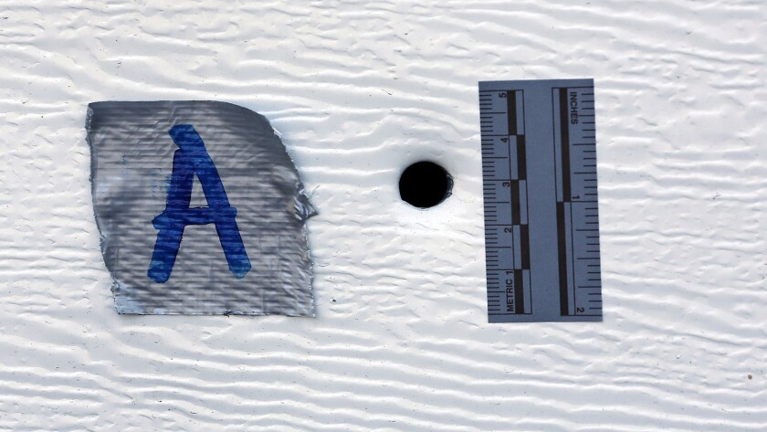 A piece of tape and ruler flank a bullet hole through a garage door in Los Feliz, where an unarmed man was shot by police Friday.