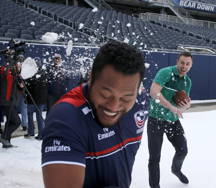 US Rugby Eagles player Andrew Suniula, left, reacts after being hit with a snowball in Chicago's Soldier Field, thrown by Ireland's Tommy Bowe, after a news conference Tuesday, Feb. 16, 2016, announcing that the Rugby World Cup champion New Zealand All Blacks will play Ireland at the historic stadi