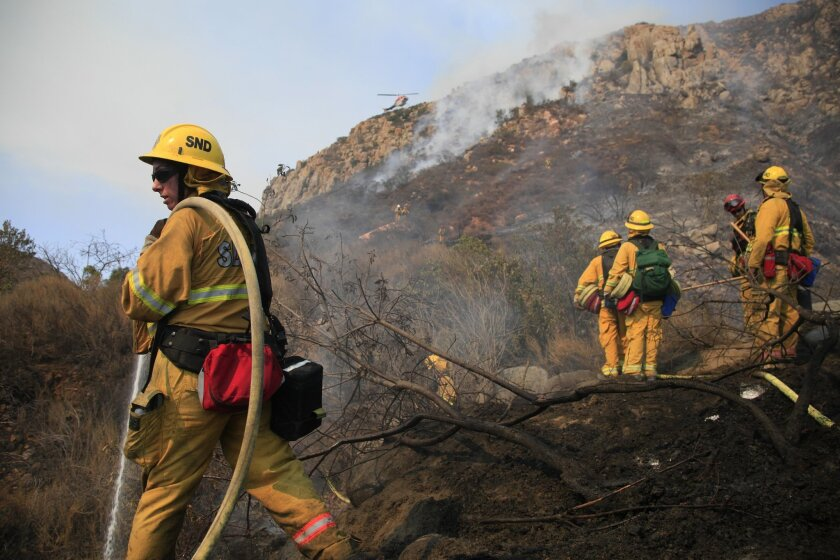 San Diego Fire Fighter/ Paramedic Amber Taddeo, left, was one of the first to respond put out hot spots as other fireman continued up the steep grade to put out the fast-moving Mission Trails fire. Helicopters and fire fighters from San Diego, San Miguel, Lakeside and Santee fought the fast moving blaze as it made its way up and over Kwaay Paay, an area popular for rock climbing.