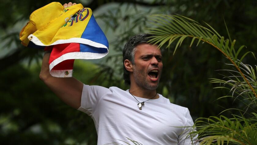Opposition leader Leopoldo Lopez holds a Venezuelan national flag as he greets supporters outside his home in Caracas on Saturday.