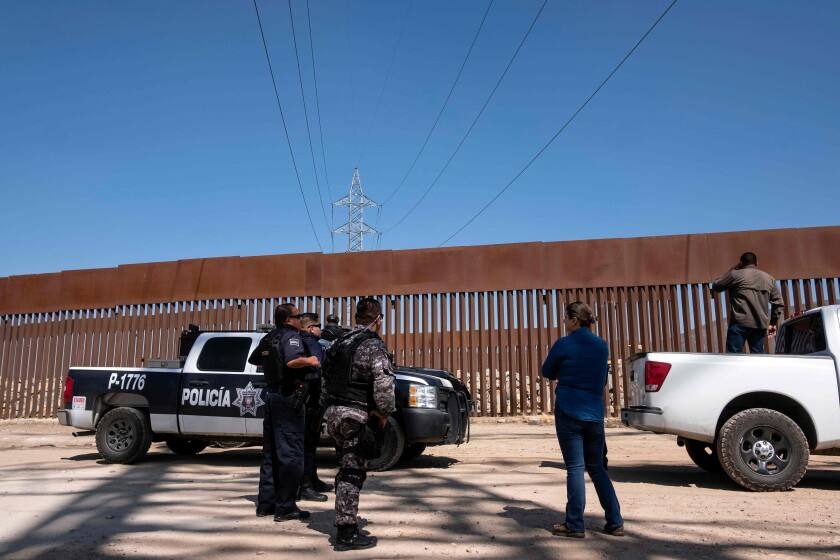 Mexican security forces patrol the U.S.-Mexico border fence