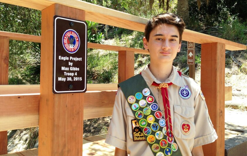 Max Gibbs with a sign on the bridge commemorating his Eagle Scout project.