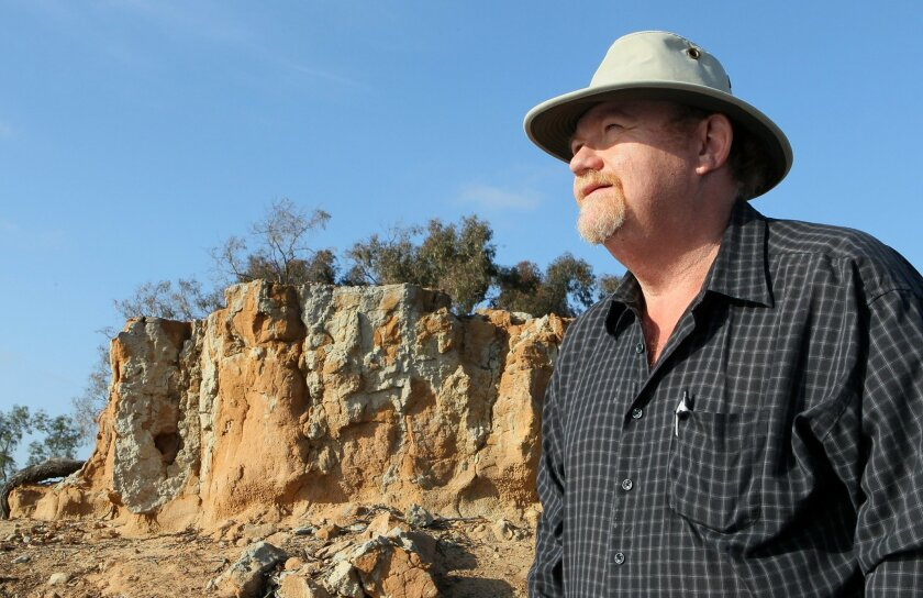 Portrait of Greg Rubin, owner of California's Own Native Landscape Design, of Escondido, with the rocky outcropping area on the space he's working on to create a native garden.