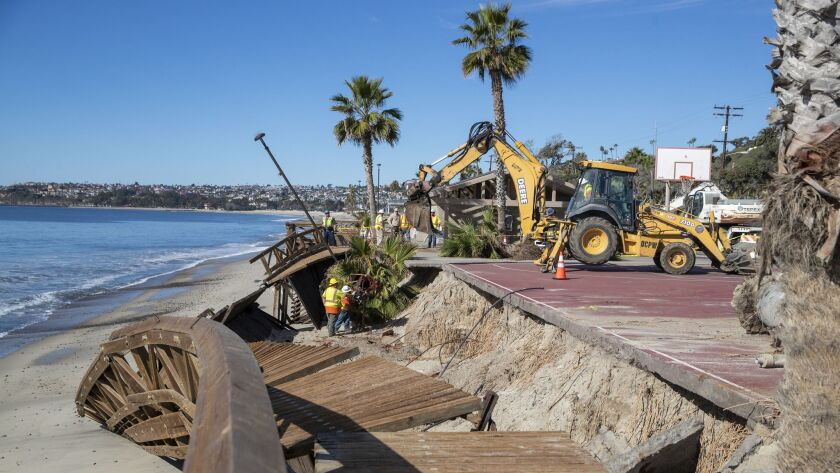 Orange County public works crews use heavy machinery to remove a damaged boardwalk at Capistrano Beach in Dana Point. Damage to coastal property is one of the greatest costs of climate change.