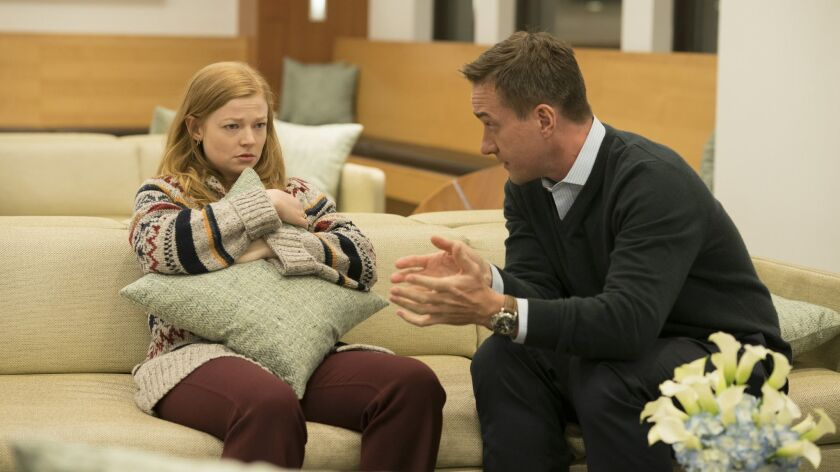 "Sarah Snook, holding a throw pillow, and Matthew Macfadyen on a couch in ""Succession."""