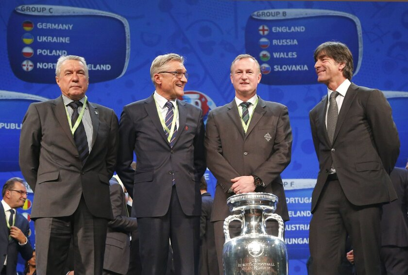 FILE - In this Saturday, Dec. 12, 2015 file photo, the coaches of teams drawn in group C, from left: Ukraine's assistant coach Volodymyr Onyshchenko, Poland's coach Adam Nawalka, Northern Ireland coach Michael O'Neill and Joachim Loew, the coach of Germany pose for a photo after the Euro 2016 socce