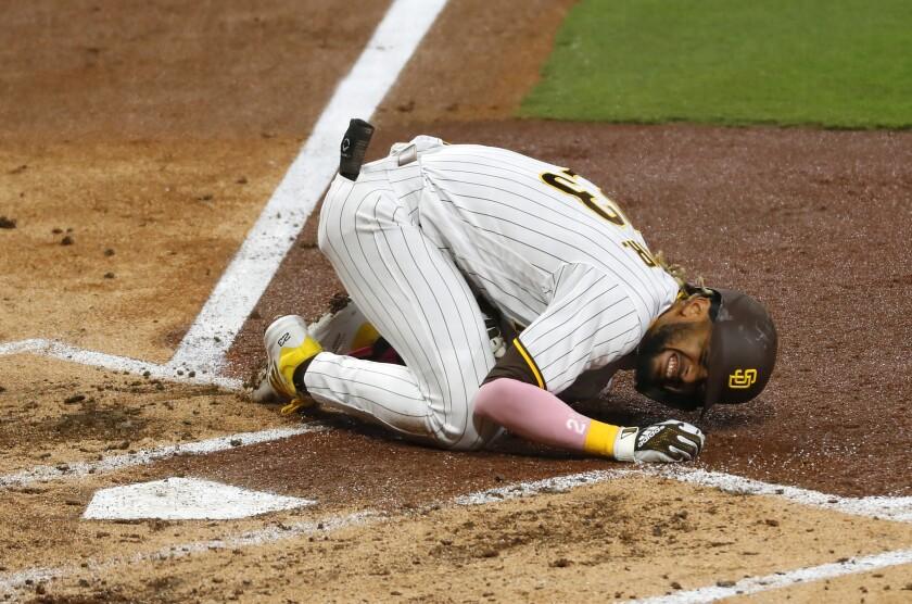 San Diego Padres' Fernando Tatis Jr. grimaces in pain.