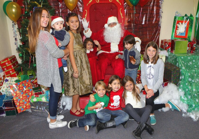 Kris Kringle meets with La Jolla families during the La Jolla Recreation Center's annual lunch with Santa, Dec. 19, 2015. Standing: Hannah Fitzcluster holding Jaden Moss, Brooke and Chloe Fitzcluster, Xander Moss. Sitting: Ryan and Reese Cleveland, Zenovia and Ruxandra Baluta