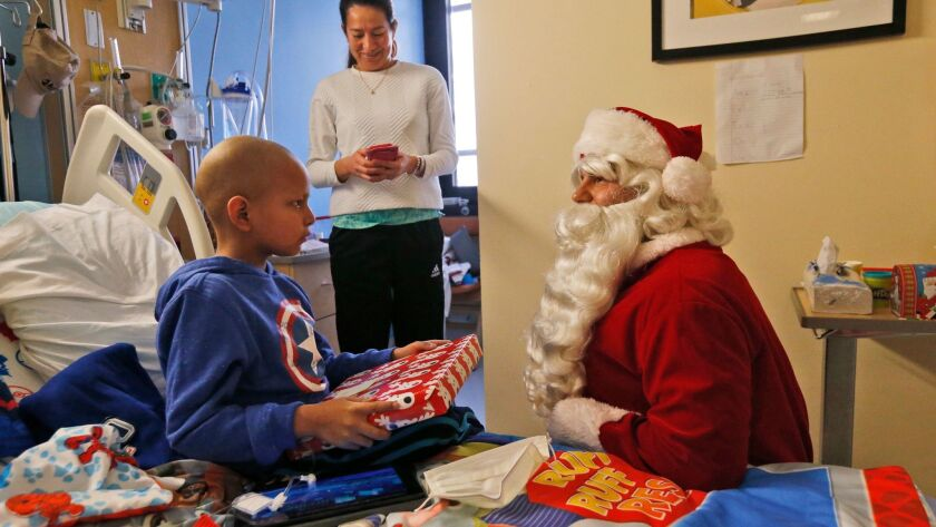 Nicolas Zapata, 6, opens a present from Santa Claus at Holtz Children's Hospital in Miami. A new study of Santa's gift-giving habits in the U.K. finds that whether hospitalized children are visited by Santa has more to do with economic status than whether they're naughty or nice.