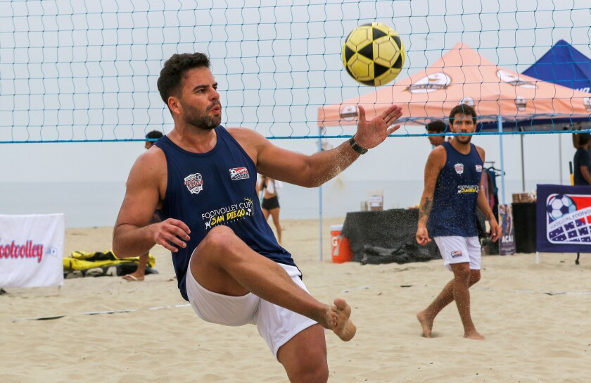 Lucas Vedoy kicks the ball over the net during a match at the Footvolley event on the beach at the warm water jetties in Carlsbad.