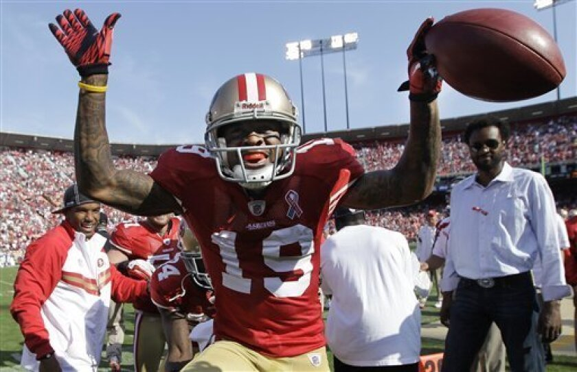 San Francisco 49ers wide receiver Ted Ginn Jr. celebrates after scoring on a 55-yard punt return for a touchdown against the Seattle Seahawks in the fourth quarter of an NFL football game in San Francisco, Sunday, Sept. 11, 2011. (AP Photo/Paul Sakuma)