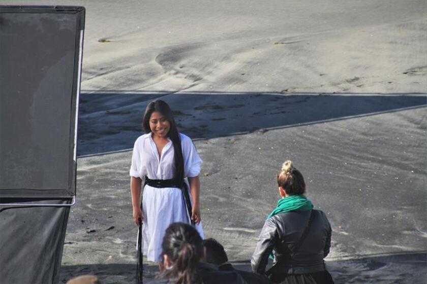 """La actriz mexicana Yalitza Aparicio (i), protagonista de la película """"Roma"""", del director Alfonso Cuarón, es vista este lunes en la valla fronteriza de Tijuana, en el estado de Baja California (México), donde realizó algunas fotografías con migrantes que permanecen aún en esa zona para intentar lograr asilo en Estados Unidos. EFE"""