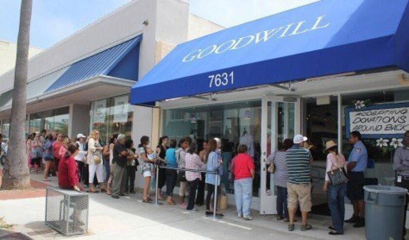 A security guard manages the flow of bargain-hunting customers lined up to enter the new Goodwill store at 7631 Girard Ave. on June 27. Pat Sherman photos
