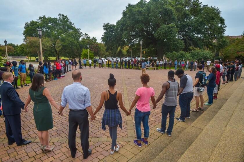 Gente rezando durante una vigilia organizada por Myron Smothers en el Memorial Tower, en el campus de la Universidad Estatal de Louisiana, en Baton Rouge, Louisiana, el lunes 11 de julio de 2016. (Scott Clause/The Daily Advertiser via AP)