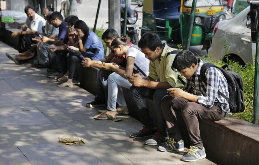 Indians use their mobile phones in New Delhi on Sept. 22.