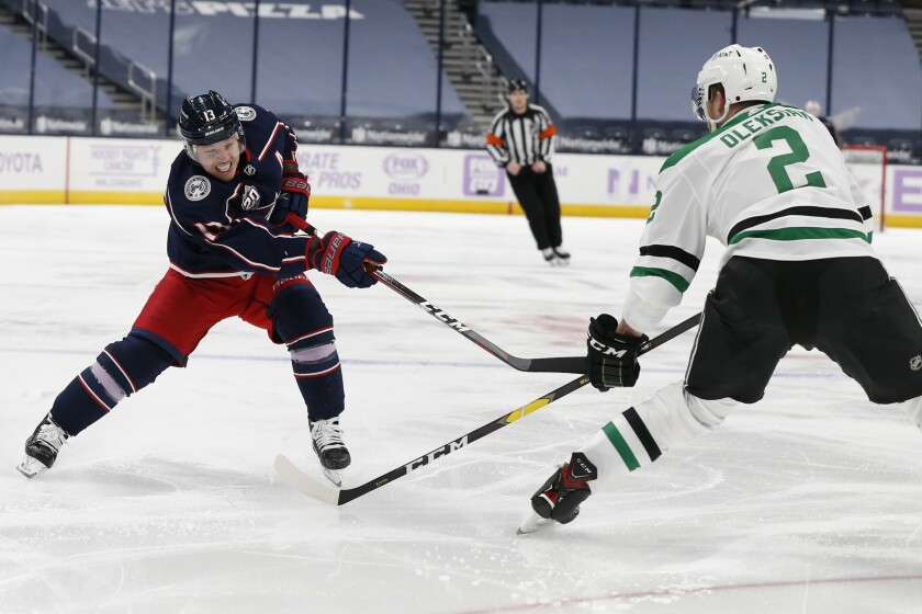 Columbus Blue Jackets' Cam Atkinson, left, shoots as Dallas Stars' Jamie Oleksiak defends during the second period of an NHL hockey game Thursday, Feb. 4, 2021, in Columbus, Ohio. (AP Photo/Jay LaPrete)