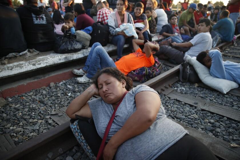 Migrantes hondureños aguardan en el puente que cruza el río Suchiate el lunes 20 de enero de 2020 con la intención de ingresar a México desde Guatemala. (AP Foto/Moisés Castillo)