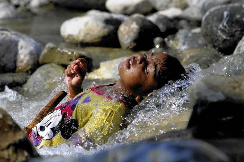 Mariah Adams, 3, of Norwalk lies in the cool running water of the San Gabriel River. The Forest Service manages the mountains, where picnic sites and trail heads are typically strewn with trash and broken glass.