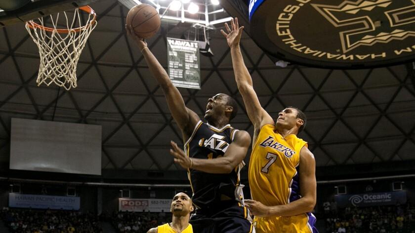 Lakers forward Larry Nance Jr. tries to block a shot by Utah Jazz guard Alec Burks during a preseason game Oct. 6 in Honolulu.