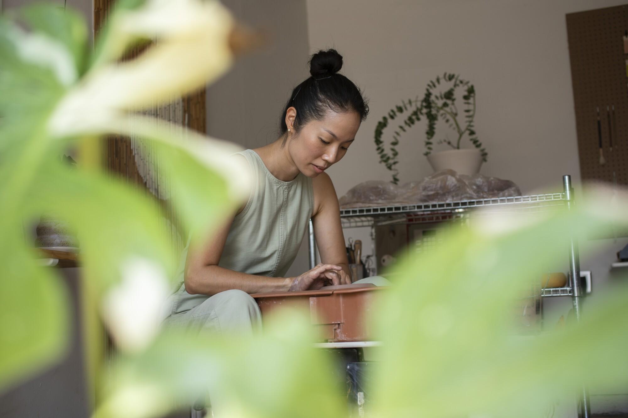 Mipa Shin throws a pot at her wheel in her garage studio.