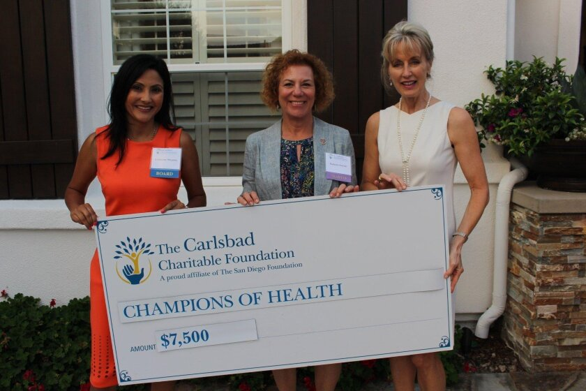 Carlsbad Charitable Foundation Grants cahirperson Catherine Magana (left) and Board Member Hollyce Phillips (right) present a grant award to Barbara Mandel of Champions of Health.