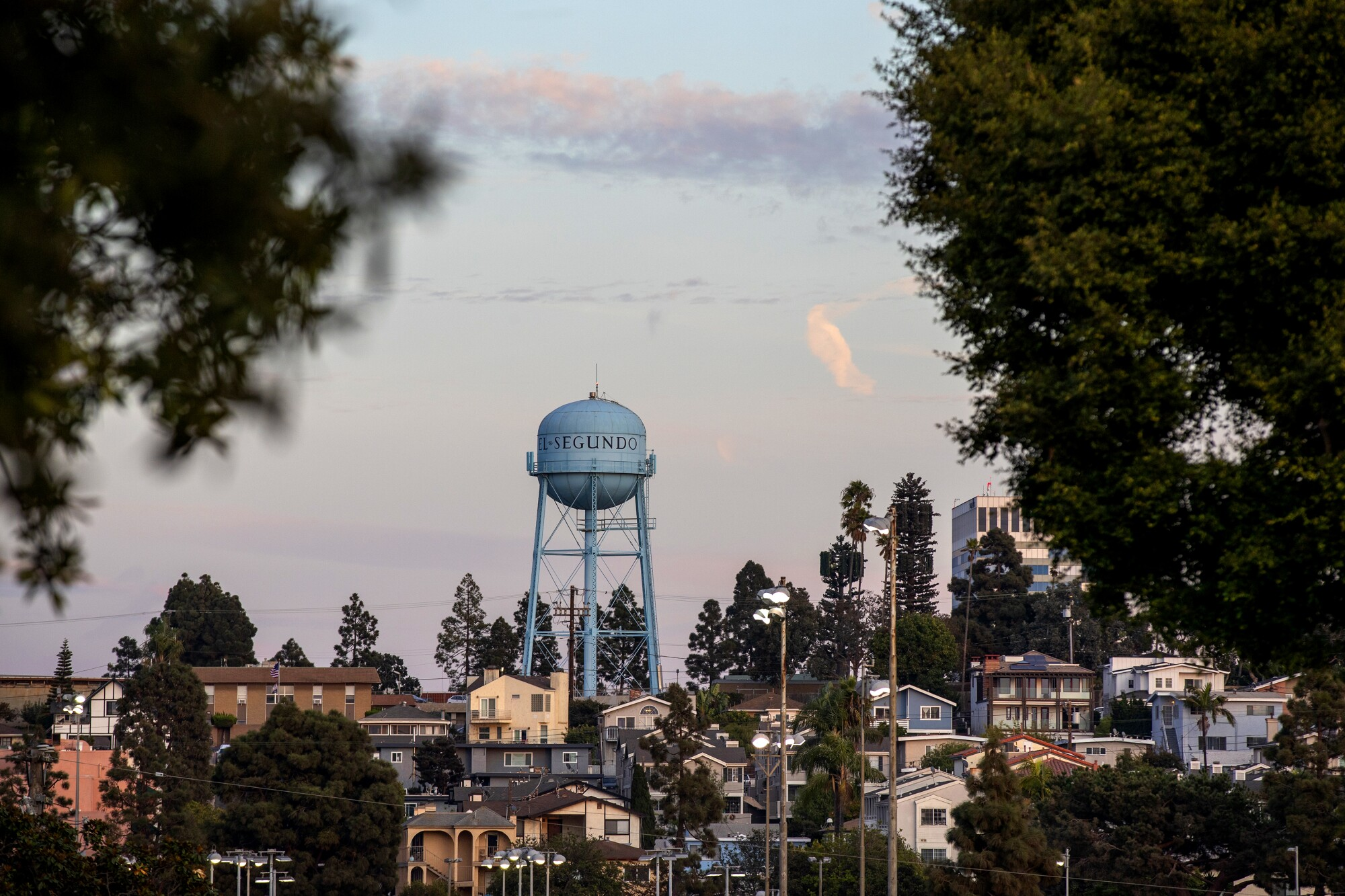 A water tower rises above a surrounding neighborhood