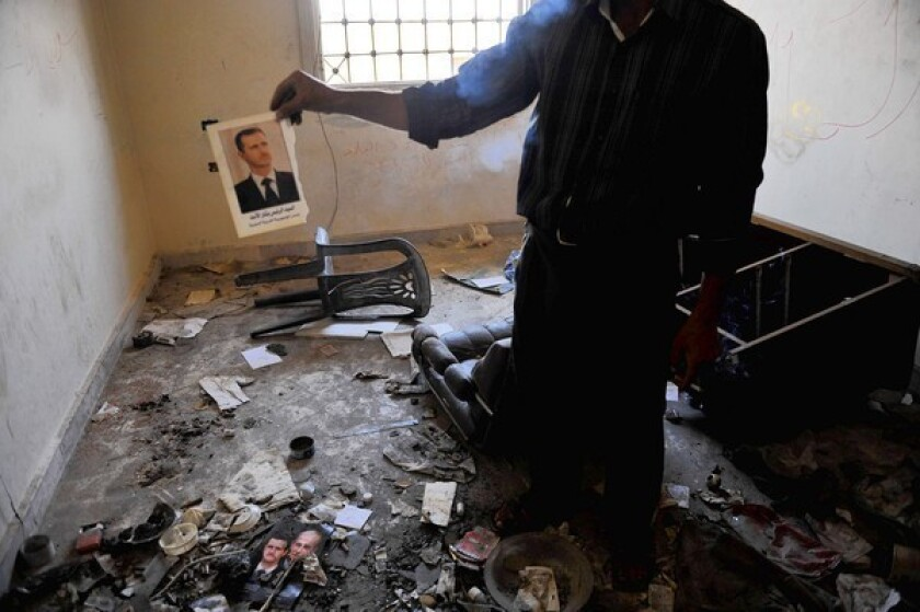 A man holds up a picture of Syrian President Bashar Assad at a former police station in Atareb after clashes between Syrian soldiers and Free Syrain Army fighters near Aleppo.
