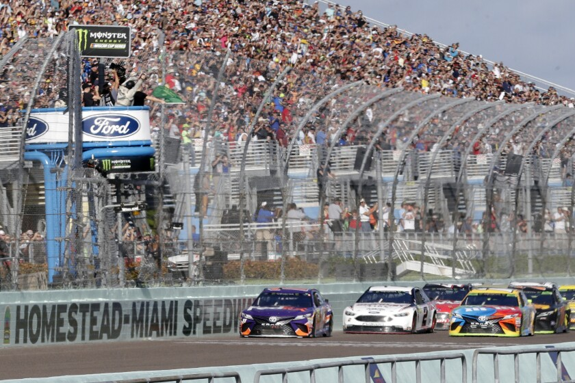 FILE - In this Nov. 18, 2018, file photo, Denny Hamlin, left, leads the pack at the start of the NASCAR Cup Series championship auto race at Homestead-Miami Speedway, in Homestead, Fla. NASCAR and IndyCar have each called off their races this weekend. NASCAR was scheduled to run Sunday at Atlanta Motor Speedway without spectators but said Friday, March 13, 2020, it is calling off this weekend and next week's race at Homestead-Miami Speedway. IndyCar was scheduled to open its season Sunday on the streets of St. Petersburg, Florida, but suspended it's season through the end of April. (AP Photo/Lynne Sladky, File)