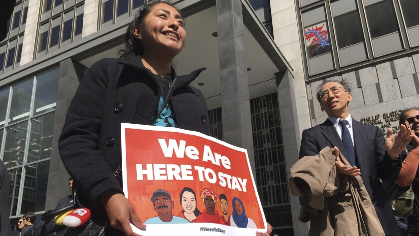 Erica Leyva with the Services, Immigrant Rights and Education Network of San Jose carries a sign outside a courthouse earlier this month when a federal judge heard arguments in the case.